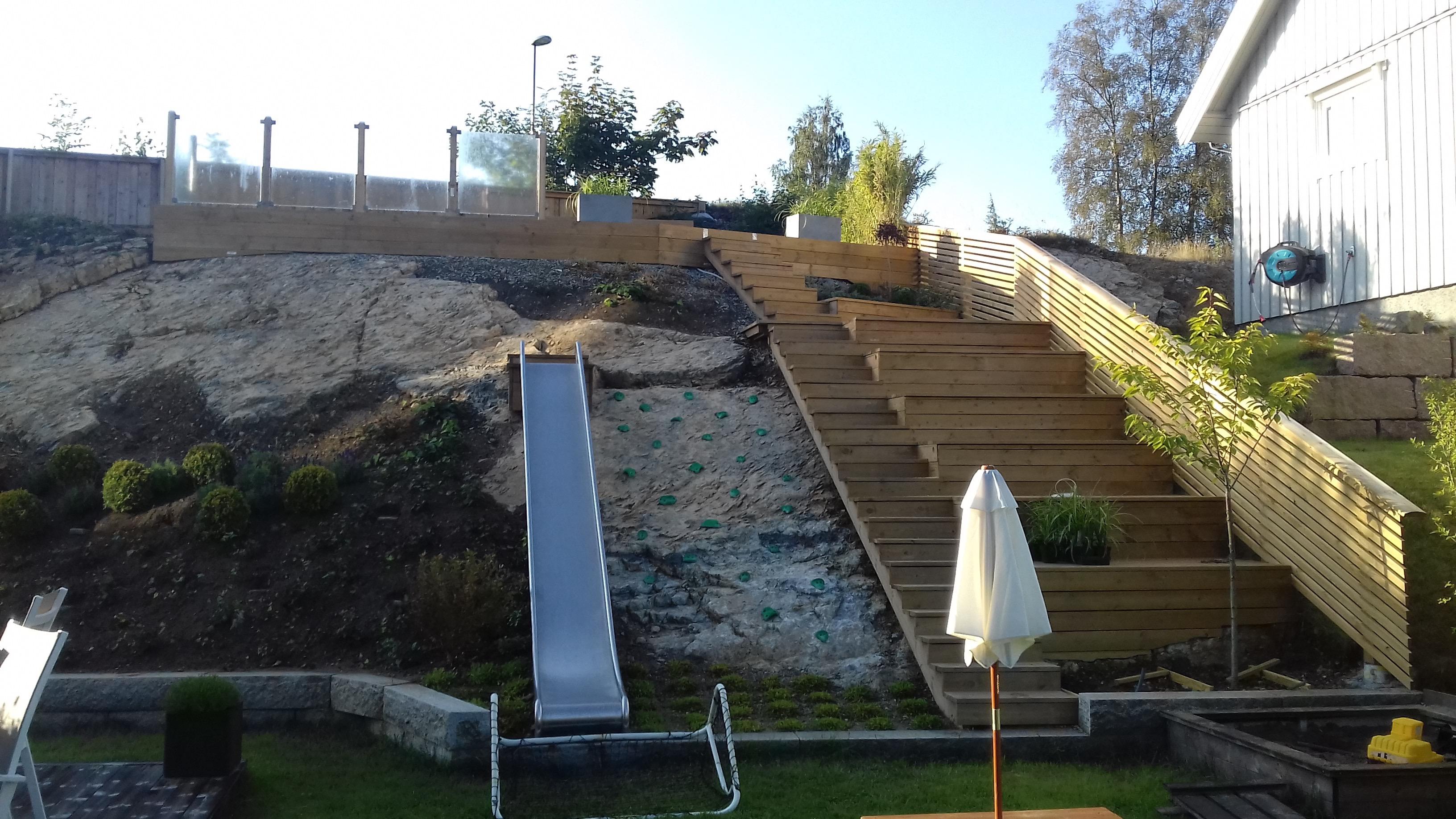 Etablere lekeområde i skråning med sklie, skråstilt klatrevegg, lekehus, trapp, terrasse.