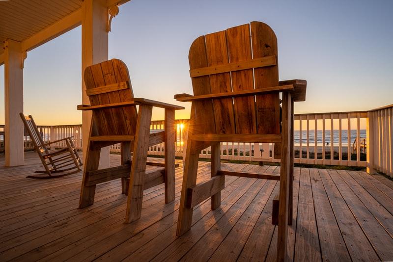 Terrasse i tre med rekkverk og trestoler vendt mot solnedgang