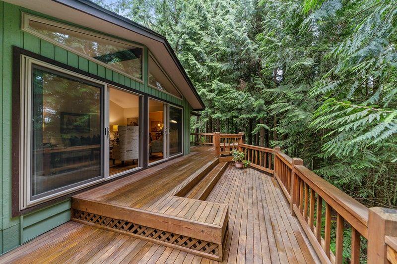 Stor terrasse som er bygget i treverk med skog rundt